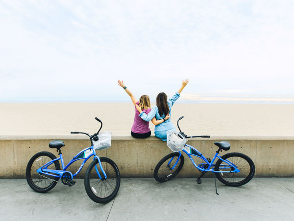 2 girls with bikes in front of beach